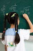A girl writing on blackboard