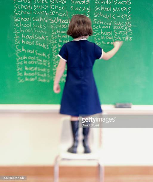 Girl (7-9) writing on chalkboard, rear view