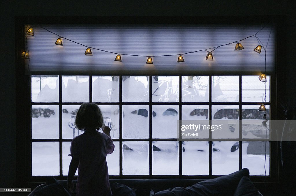 Girl (4-6) writing on frosty window, rear view, dawn, winter : Stock Photo