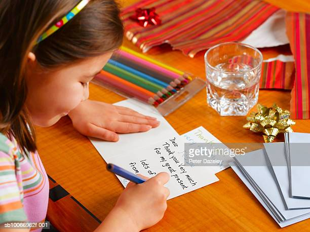 Girl (6-7) writing Thank You card, smiling
