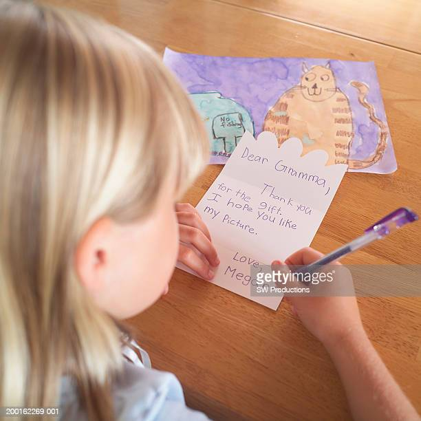 Girl (7-9) writing thank you card to grandmother, rear view