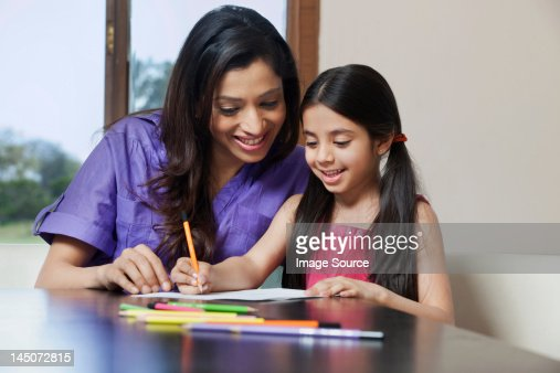 Girl writing while her mother looks on