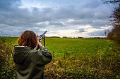 Girl with shotgun skeet shooting on a field in the sunset