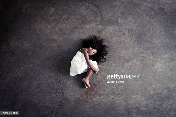 Girl-child curled up, resting, neutral background