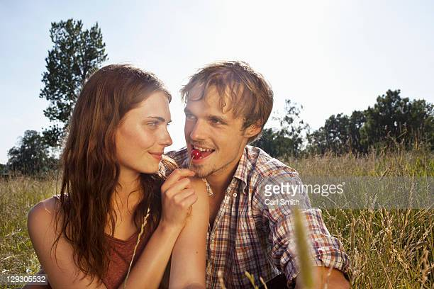 Girlfriend feeds her boyfriend a cheery amongst the timothy grass