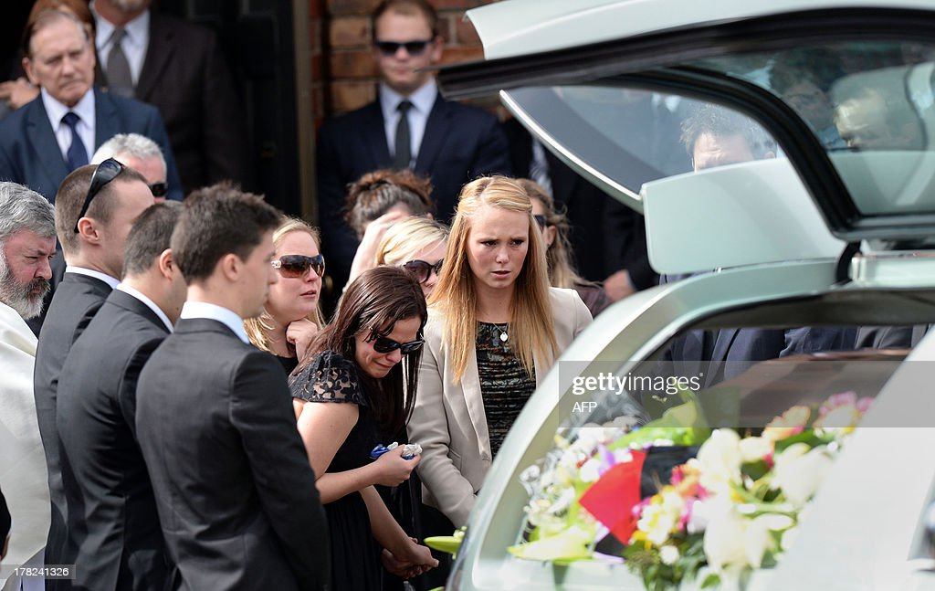 Girlfriend Sarah Harper (R) and family members of Australian baseball player Chris Lane, who was killed in the small Oklahoma town of Duncan in the US, look at Lane's coffin as they leave St Therese's Parish after attending his funeral in Melbourne on August 28, 2013. Lane, 22, was in the US on a baseball scholarship and was jogging in Duncan when he was shot in the back and left to die on the side of the road on August 16. Two teenagers, aged 15 and 16, have been accused of shooting Lane, while a third, aged 17, was charged with use of a vehicle in the discharge of a weapon and acting as an accessory after the fact. AFP PHOTO / Mal Fairclough
