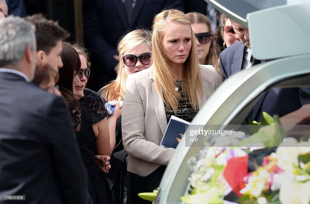 Girlfriend Sarah Harper (front R) joins family members of Australian baseball player Chris Lane, who was killed in the small Oklahoma town of Duncan in the US, as they leave St Therese's Parish after attending Lane's funeral in Melbourne on August 28, 2013. Lane, 22, was in the US on a baseball scholarship and was jogging in Duncan when he was shot in the back and left to die on the side of the road on August 16. Two teenagers, aged 15 and 16, have been accused of shooting Lane, while a third, aged 17, was charged with use of a vehicle in the discharge of a weapon and acting as an accessory after the fact. AFP PHOTO / Mal Fairclough