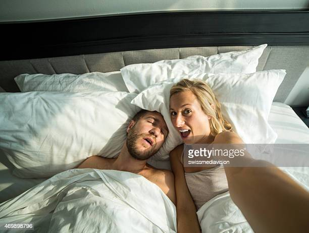 Girlfriend takes selfie of boyfriend sleeping in bed