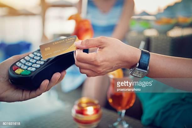 Amigas están pagando sus cócteles en la playa de la barra usando tarjeta de crédito sin contacto
