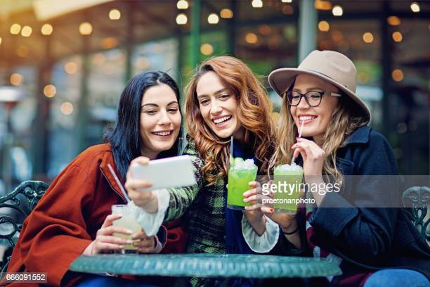 Girlfriends are taking selfie in a cafeteria