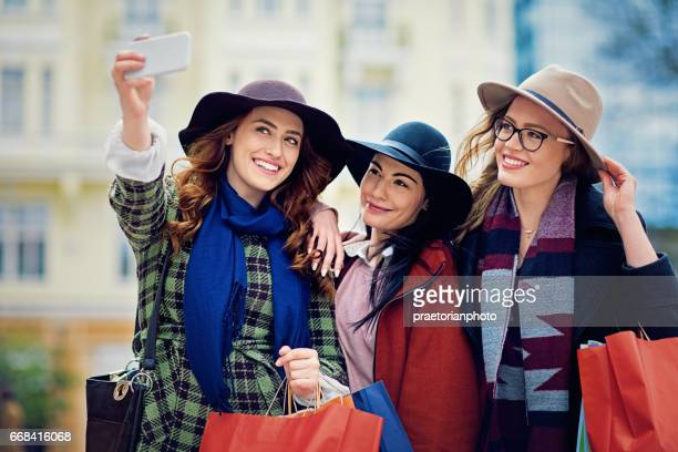 Girlfriends are taking selfie on the street with shopping bags in their hands