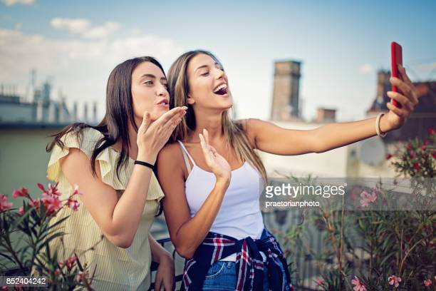 Girlfriends are taking selfie/making video call on the roof terrace