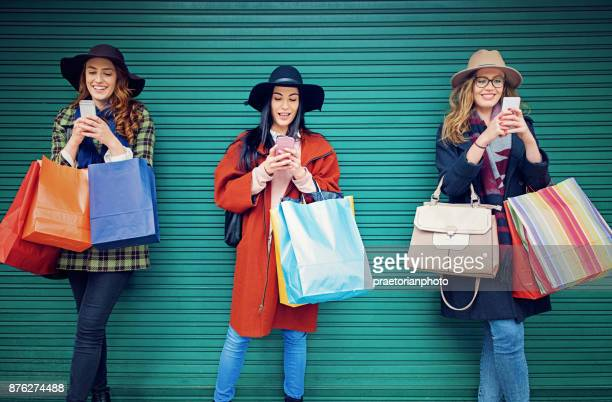 Girlfriends are texting using their mobile phones with a shopping bags