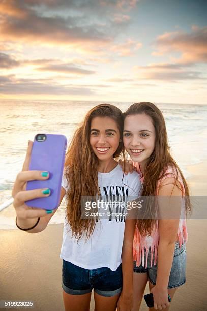 girlfriends at the beach taking 'selfies' photos