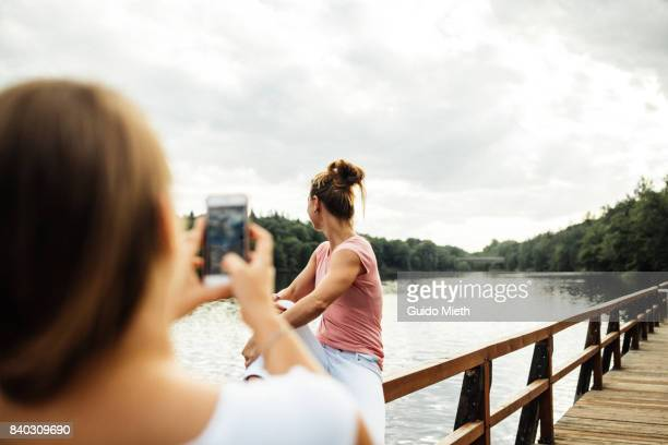 Girlfriends doing selfies outdoor.