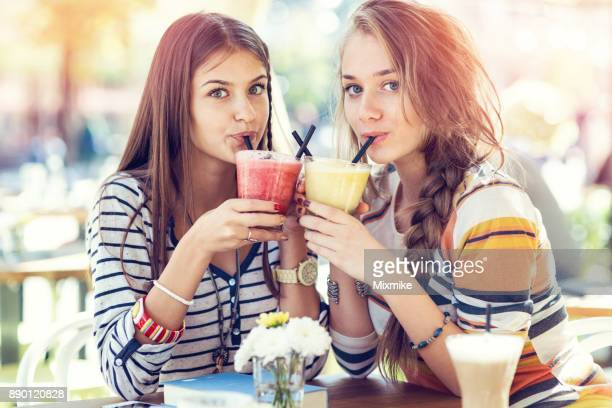 Girlfriends drinking fresh juices outdoors