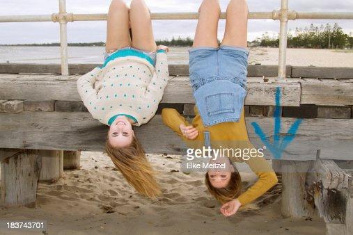 Girlfriends hanging upside down from pier