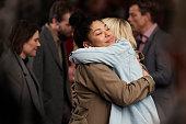 Girlfriends hugging among busy crowd