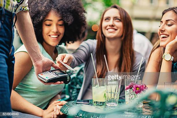 Girlfriends in cafe making payment