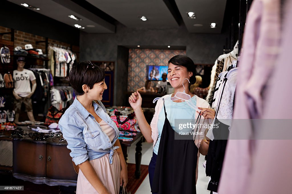 Girlfriends laughing together, while shopping : Stock Photo