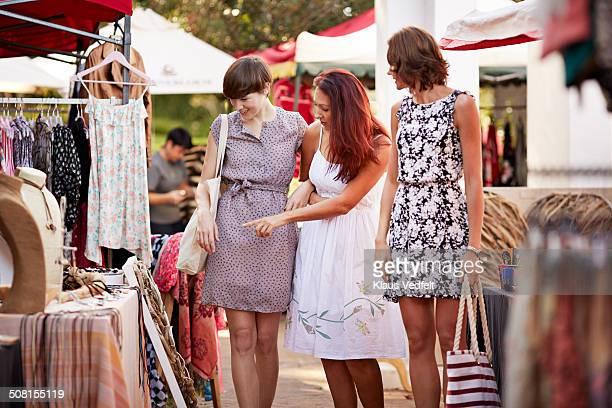 3 girlfriends looking at clothes at market