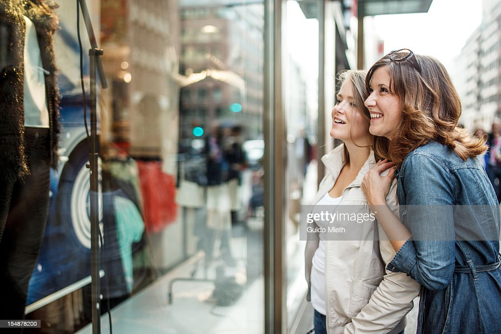 Girlfriends looking into a shop window. : Stock Photo