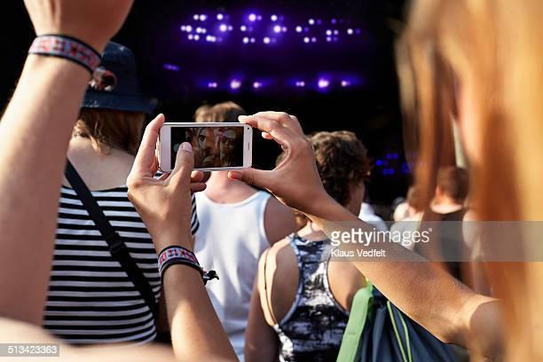 Girlfriends making selfie at concert