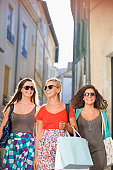 Girlfriends shop in streets with bags