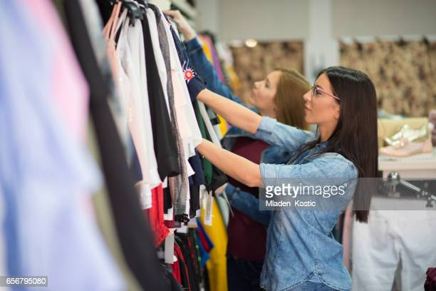 Girlfriends shopping together in clothing store