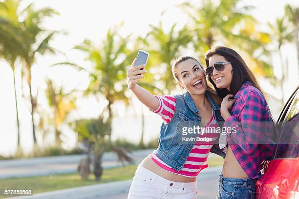 Girlfriends taking photos with their smart phone at beach, Miami, Florida, USA