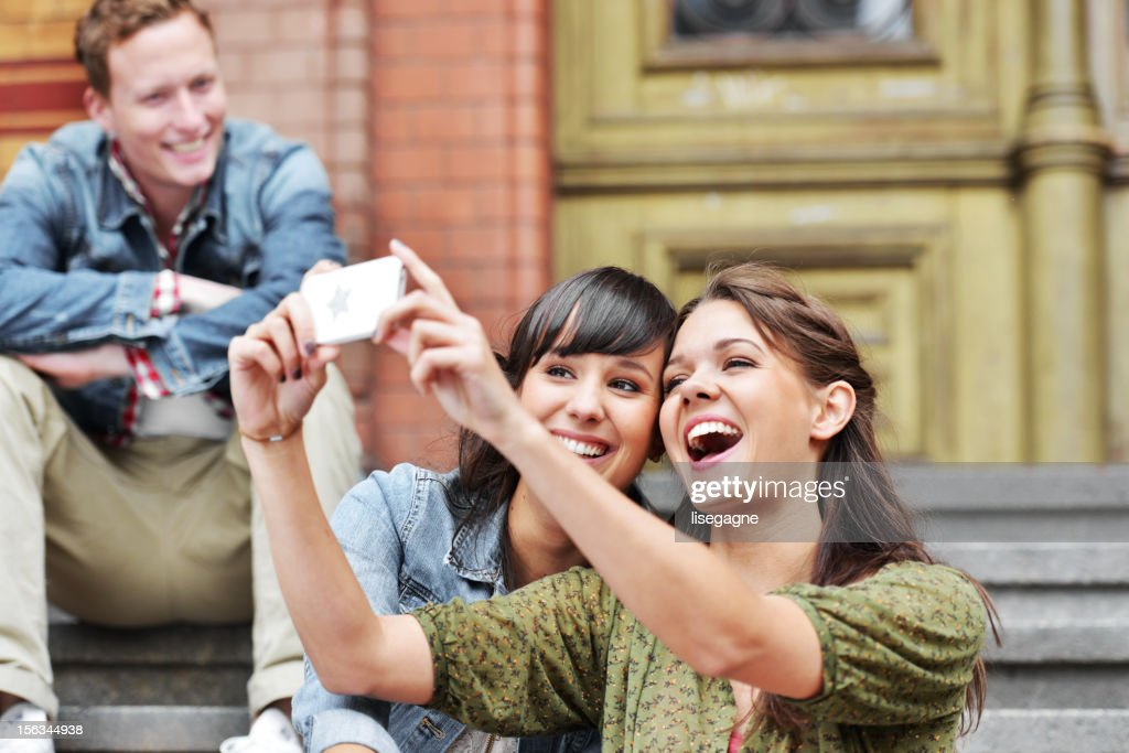 Girlfriends taking picture with smartphone : Stock Photo