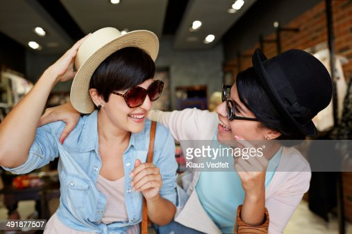 Girlfriends trying hats & glasses and having fun