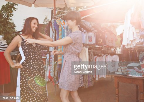 Girlfriends trying on dresses at market