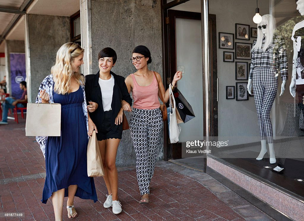 Girlfriends walking together with shopping bags