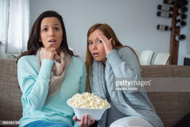 Girlfriends watching horror movie on TV
