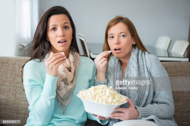 Girlfriends watching suspense TV show, movie, together on a sofa