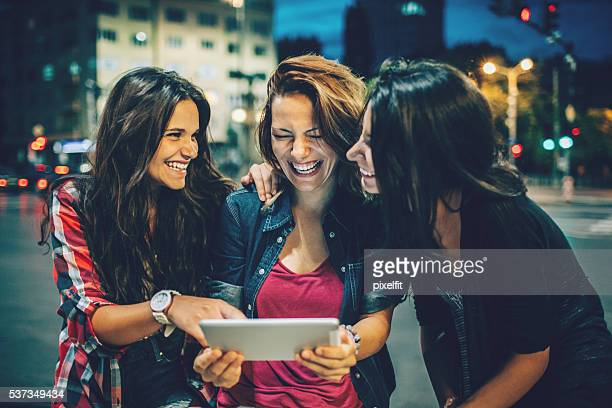 Girlfriends with digital tablet out at night
