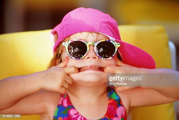 Girl(2-4)in swimming costume,cap & sunglasses,pulling face,close-up