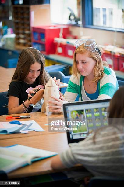 girls [11] in classroom working on model rocket