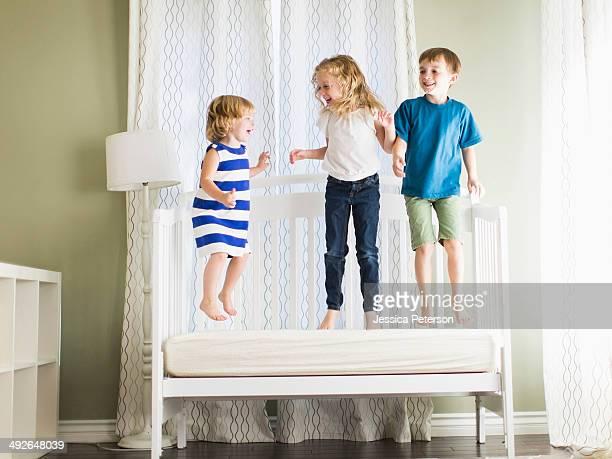 Girls (4-5, 6-7) and boy (8-9) jumping on sofa, Los Angeles, California, USA