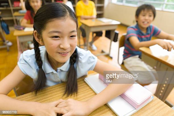 Girls and boys in classroom, smiling and sitting at desk