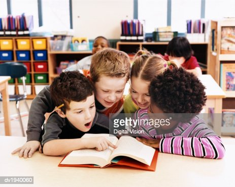 Girls and Boys Looking at the Same Textbook in a Classroom at Primary School : Stock-Foto