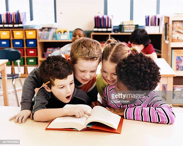 Girls and Boys Looking at the Same Textbook in a Classroom at Primary School