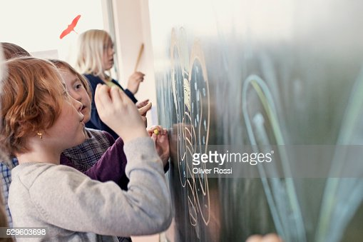 Girls and boys (6-7) painting in art class : Stock Photo