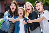 Girls and boys teenagers friends posing with thumbs up outdoors