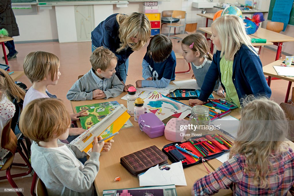 Girls and boys (6-7) taking part in art class : Foto de stock