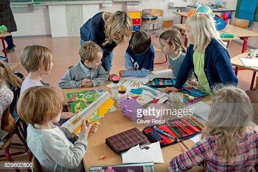 Girls and boys (6-7) taking part in art class : Stock Photo