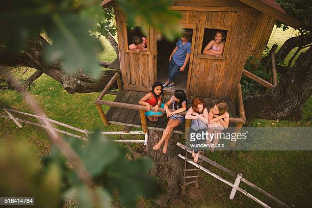 Girls and boys talking and playing in a wooden treehouse