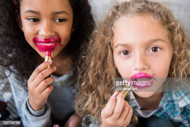 Girls applying messy lipstick