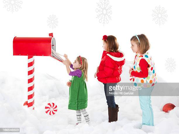 Girls (4-5,6-7) are helping sister (18-23months) to send letter